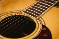 在声学吉他下fretboard的宏观射击有浅景深的 免版税库存照片