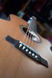 在声学吉他下fretboard的宏观射击有浅景深的 库存图片