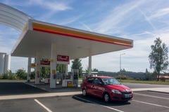 在壳加油站的红色斯柯达法比亚汽车 免版税库存照片
