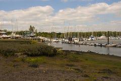 在处于低潮中艰苦小圆盾的泥滩在比尤利河在汉普郡,英国有在他们的停泊的小船的 库存照片