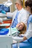 在处理以后的牙科医生愉快的妇女 库存图片