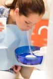 在处理以后的牙齿耐心的妇女唾液水 库存图片