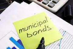 在备忘录棍子和文件写的市政债券 免版税库存照片