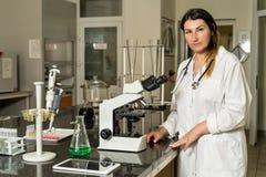 在复合显微镜旁边的中年女性化验员身分 免版税库存图片