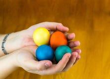 在复活节假日绘的鸡蛋在手的棕榈在一个木背景特写镜头的 免版税库存照片