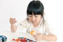 在复活节彩蛋的亚洲儿童绘画 免版税图库摄影