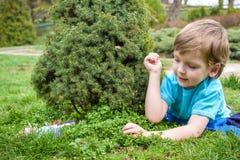 在复活节彩蛋的孩子在开花的春天庭院里寻找 搜寻五颜六色的鸡蛋的孩子在花草甸 小孩男孩和他的brot 免版税库存图片