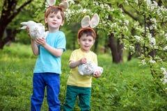 在复活节彩蛋的孩子在开花的春天庭院里寻找 搜寻五颜六色的鸡蛋的孩子在花草甸 小孩男孩和他的brot 库存图片