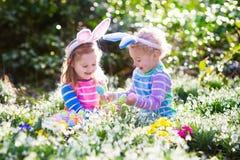 在复活节彩蛋的孩子在开花的春天庭院里寻找 免版税库存照片