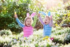 在复活节彩蛋的孩子在开花的春天庭院里寻找 库存照片