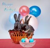 在复活节彩蛋附近,在一个大篮子的两只兔子 免版税库存图片