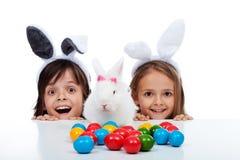 在复活节时间的愉快的孩子用他们的白色兔子 免版税库存图片