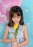 在复活节的美丽的女孩赞赏的郁金香 库存图片
