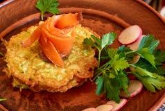 在夏南瓜薄煎饼顶部的新鲜的三文鱼用荷兰芹和萝卜 免版税库存图片