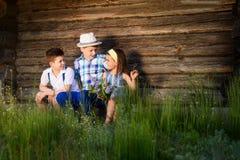 在夏天一起演奏的三个孩子 兄弟和姐妹画象在村庄 免版税库存照片