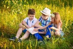 在夏天一起读的三个孩子 兄弟和姐妹画象在村庄 库存图片