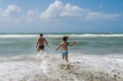在夏天休假期间,年轻爸爸和女儿游泳和戏剧在海 图库摄影