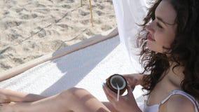 在夏天休息的女孩饮用的鸡尾酒在手段,美丽的在岸海,在手妇女的椰子的夫人挥动的你好手, 股票录像