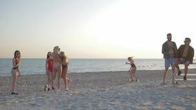在夏天使比赛,女孩在人朋友前面的戏剧排球靠岸海边的 股票录像