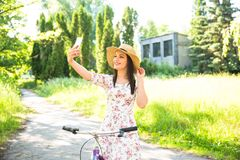 在夏天公园的愉快的相当女孩骑自行车和selfie 愉快在城市放松时间 美丽的妇女,晴天 免版税库存照片