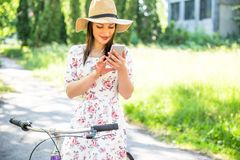 在夏天公园的愉快的相当女孩骑自行车和selfie 愉快在城市放松时间 美丽的妇女,晴天 免版税库存图片