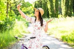 在夏天公园的愉快的相当女孩骑自行车和selfie 愉快在城市放松时间 美丽的妇女,晴天 免版税图库摄影