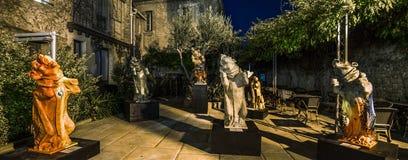 在夏天咖啡馆的哥特式妖怪雕塑从事园艺,夜视图 库存照片