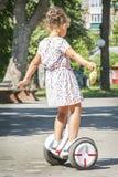 在夏天在公园,女孩在segway的白色滑冰 图库摄影