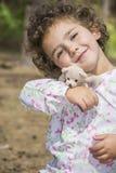 在夏天在森林一个小卷曲女孩拥抱s的玩具 免版税库存照片