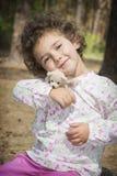 在夏天在森林一个小卷曲女孩拥抱s的玩具 免版税库存图片