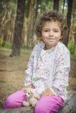 在夏天在森林一个小卷曲女孩拥抱s的玩具 免版税图库摄影