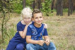 在夏天在森林一个小男孩拥抱女孩 免版税库存图片