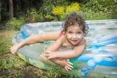 在夏天在水池的庭院坐一小英俊 图库摄影