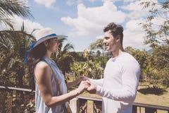 在夏天大阳台或阳台愉快的妇女和人的年轻夫妇立场Hodling手在热带森林 库存图片