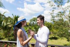 在夏天大阳台的愉快的男人和妇女Hodling手立场或在热带森林的阳台年轻有吸引力的夫妇 库存照片