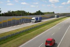 在夏天太阳的高速公路,移动有压制发动机的声音盘区的一个隧道的车 免版税图库摄影