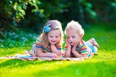 读在夏天庭院里的两个孩子 免版税库存图片