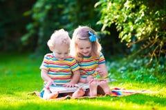读在夏天庭院里的两个孩子 库存图片