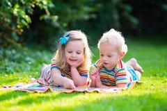 读在夏天庭院里的两个孩子 库存照片