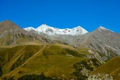 在夏天斯诺伊Mkinvari峰顶视图的高加索山脉从Gudauri 免版税图库摄影