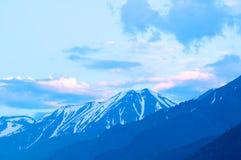 在夏天日落和蓝天的积雪覆盖的山 免版税库存图片