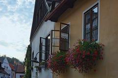 在夏天日落期间, Windows用在花箱子的红色花装饰了 捷克克鲁姆洛夫,捷克老镇  库存照片