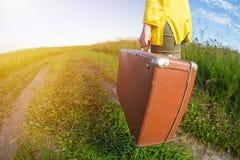 在夏天日落期间,少妇运载在领域路的棕色葡萄酒手提箱 汽车城市概念都伯林映射小的旅行 库存图片