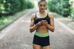 在夏天早晨公园听到在智能手机的音乐的妇女赛跑者使用蓝牙耳机 跑步女性健身的女孩  免版税库存照片
