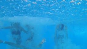 在夏天期间,快活的美丽的女朋友到有可膨胀的圆环的游泳衣里在昂贵的手段的游泳池边潜水 影视素材