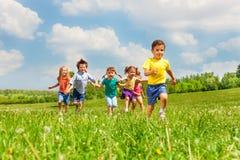 在夏天期间,在绿色领域的连续孩子 免版税库存照片
