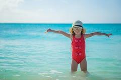 在夏天期间,帽子的可爱的小女孩在海滩 免版税库存照片