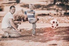 在夏天期间,生踢与他的儿子的橄榄球 库存照片