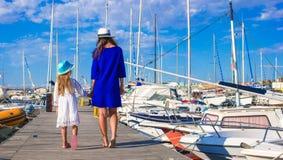 在夏天期间,年轻母亲和小女孩口岸的 免版税库存图片