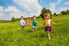 在夏天期间,绿色领域的连续孩子 免版税库存照片